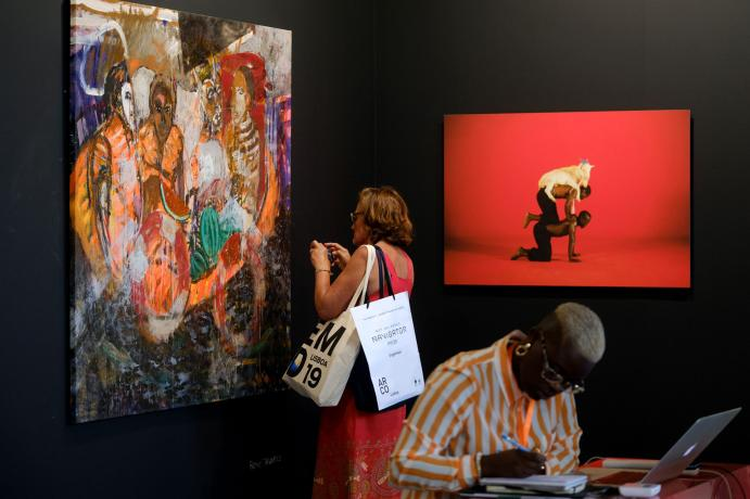 People admiring a painting at the exhibition
