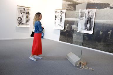 Mujer de pie observando una pieza artística de cristal