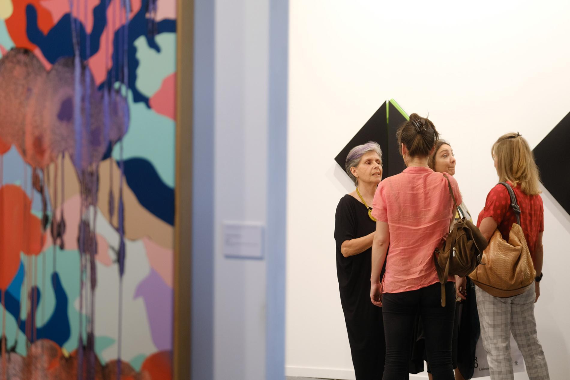 Grupo de mujeres hablando frente a una pintura