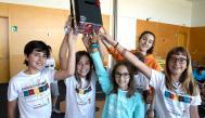 Grupo de chicos y chica alzando un trofeo