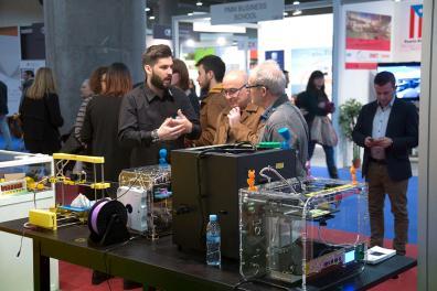 Dos profesores escuchan a un expositor mostrando su producto