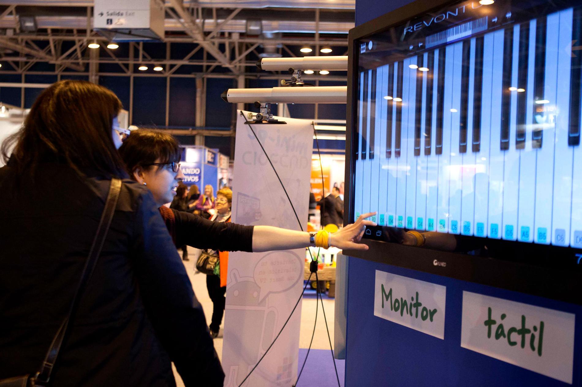 Visitantes probando un monitor tactil