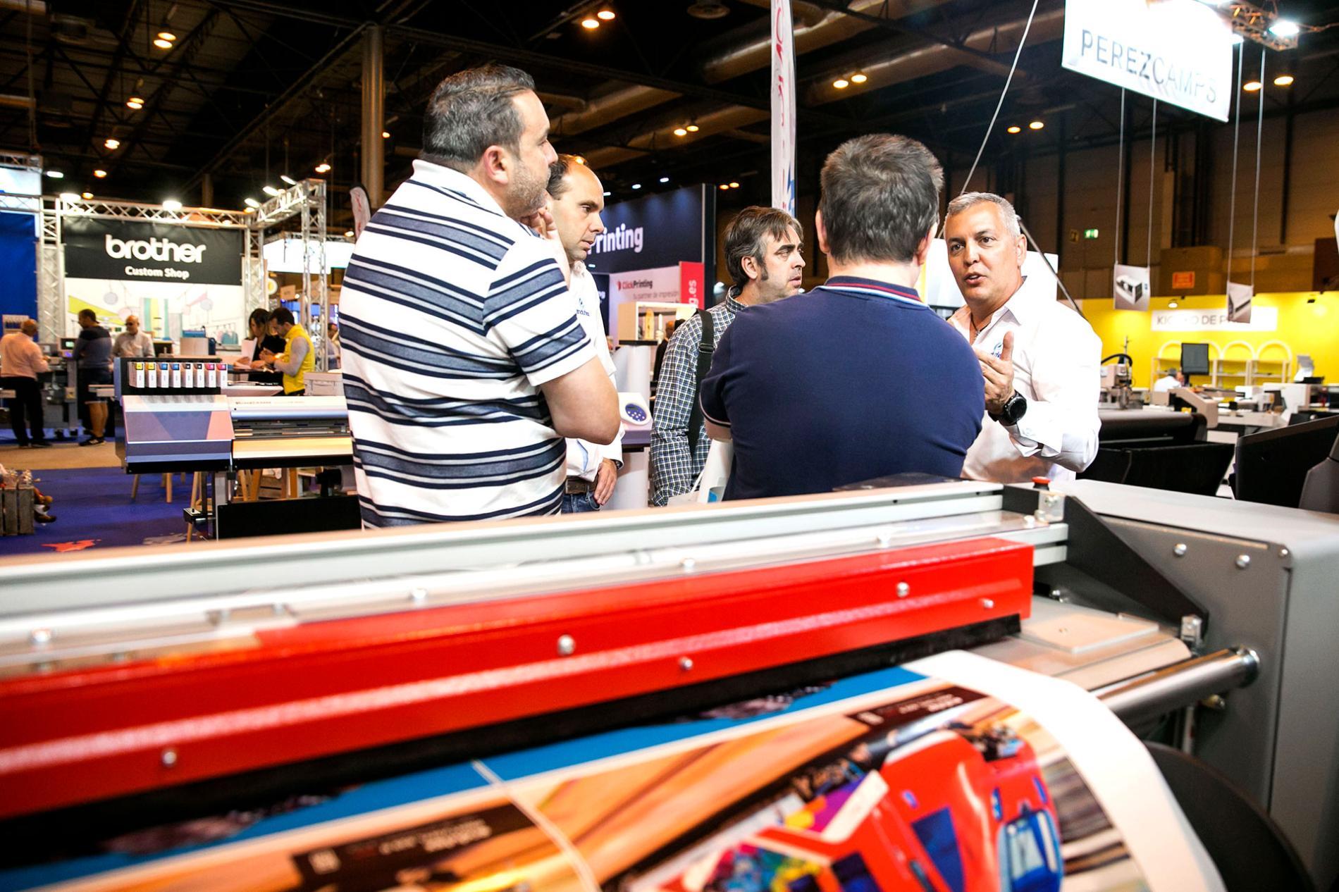Expositores conversando tras una maquina de impresion digital