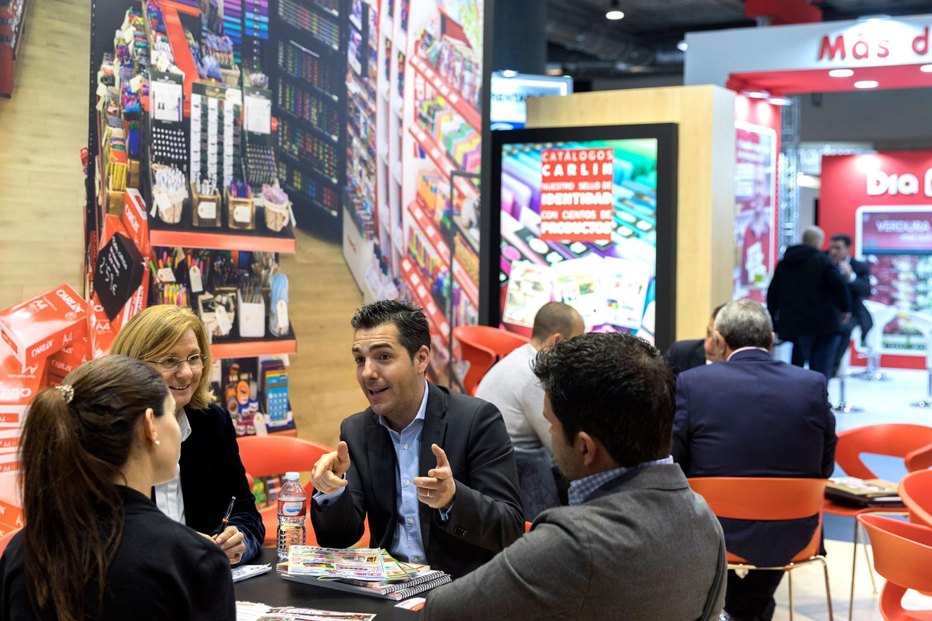 Expositores frente a un stand especializado en franquicias de material de oficina