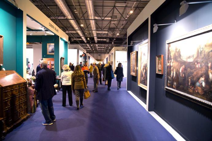 Visitantes observando pinturas en la feria
