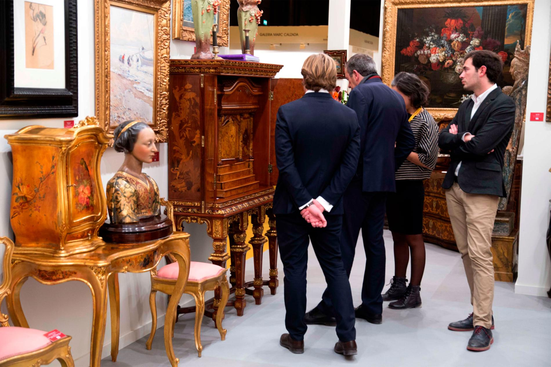 Visitors looking at antique furniture