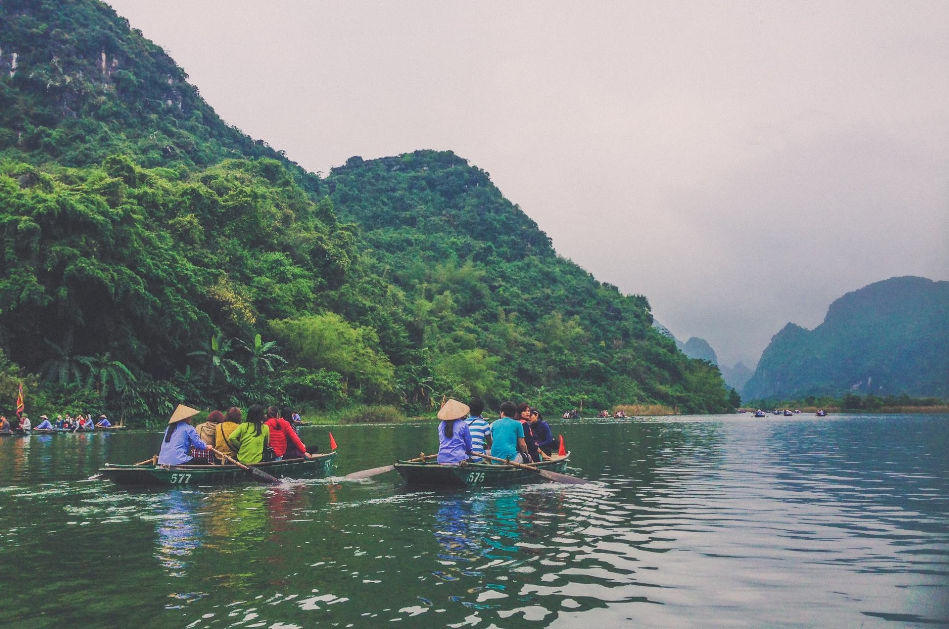 Piraguas navegando en un río bajo la invitación para participar en  FiturNext