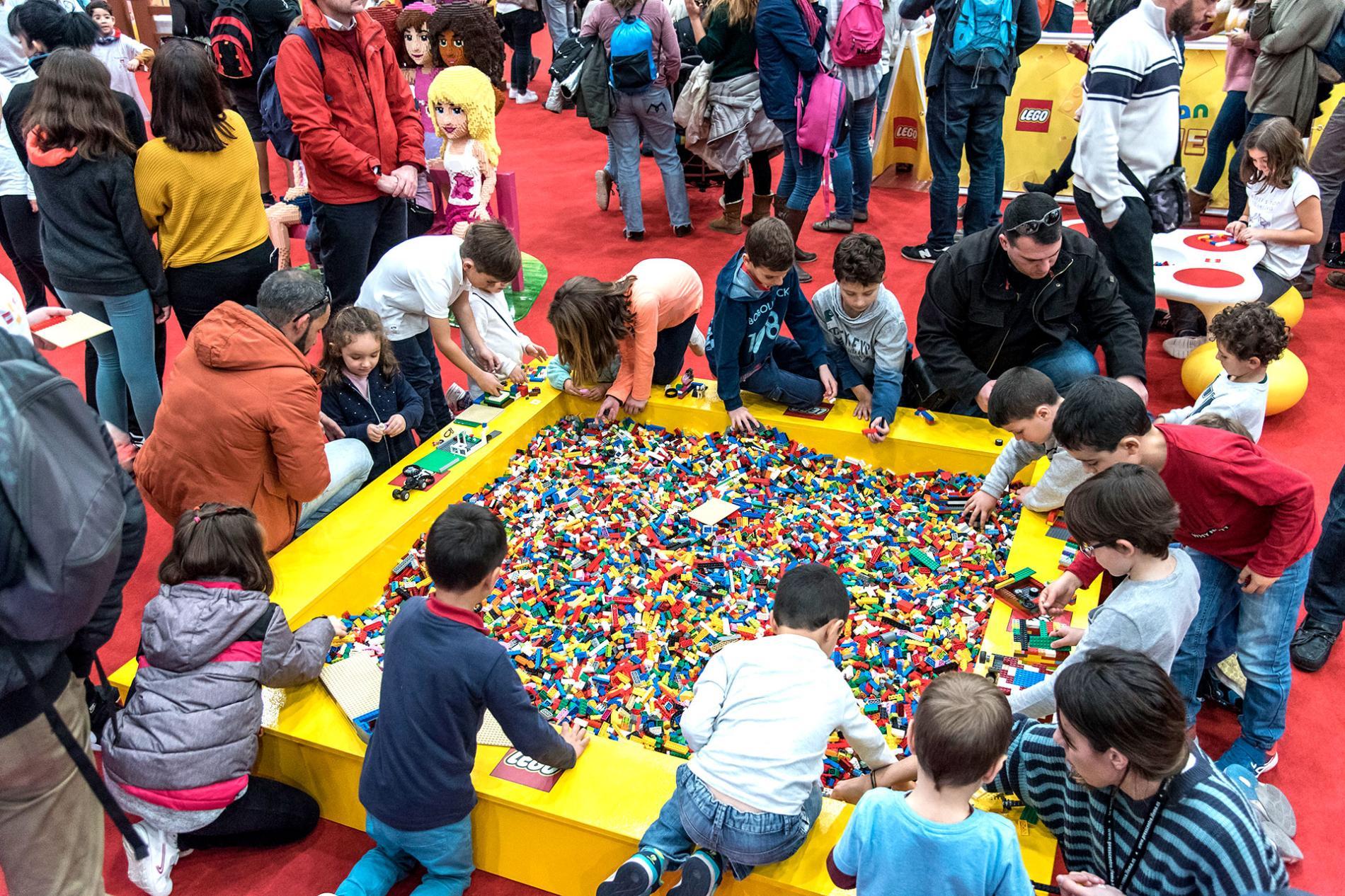 Padres y madres junto con sus hijos en un parque de figuras Lego