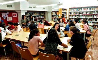 estudiantes conversando en la biblioteca
