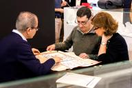 Exhibitor showing jewelry to visitors at IFEMA