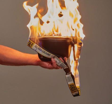 bolso ardiendo sujetado por una mano