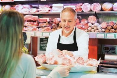 Carnicero ofreciendo productos a una clienta