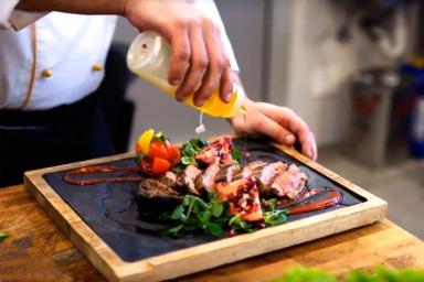 Chef aliñando con aceite unas carnes