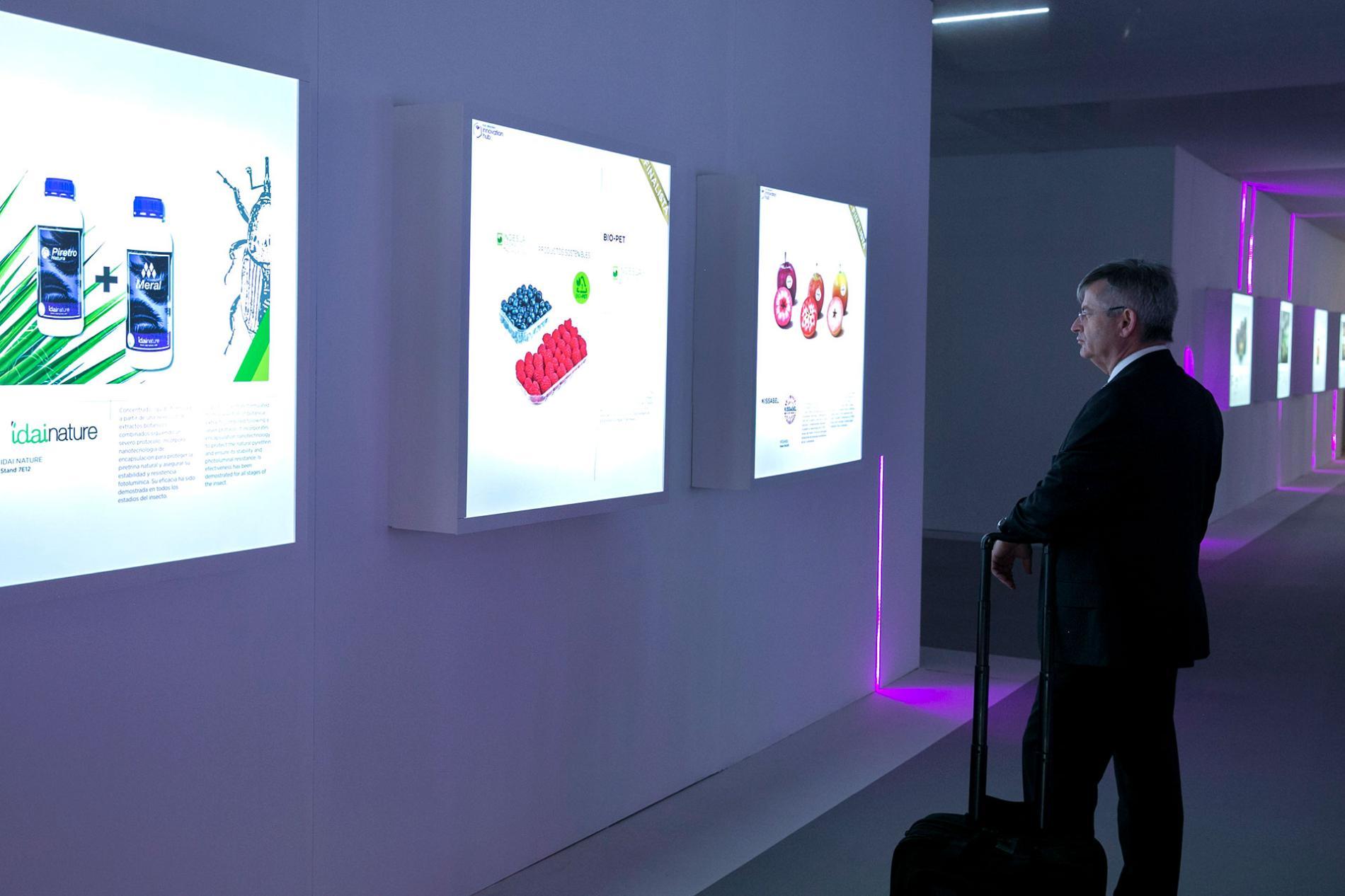 Visitante de la feria observando unos paneles luminosos con información