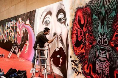 artistas pintando un graffitti en la pared