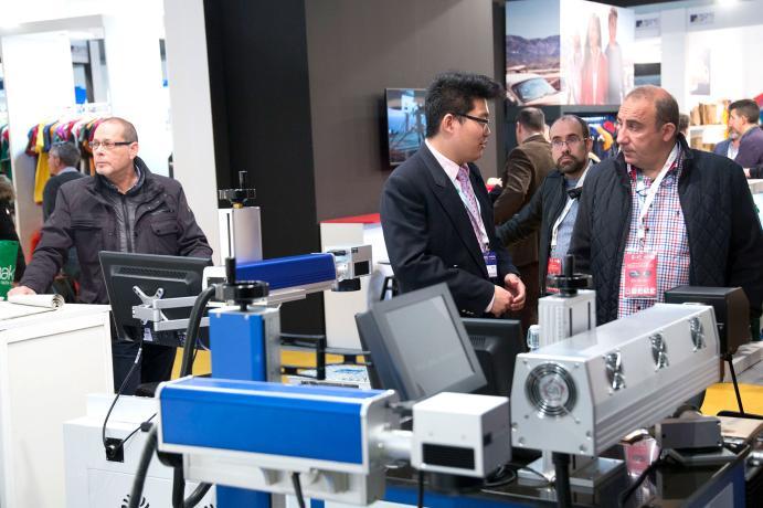 Visitantes frente a una maquina de impresion
