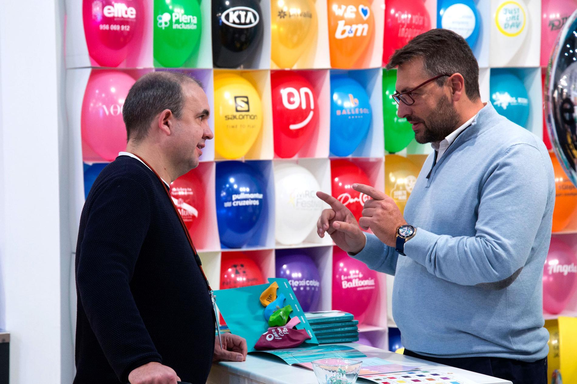 Profesionales conversando junto a globos promocionales