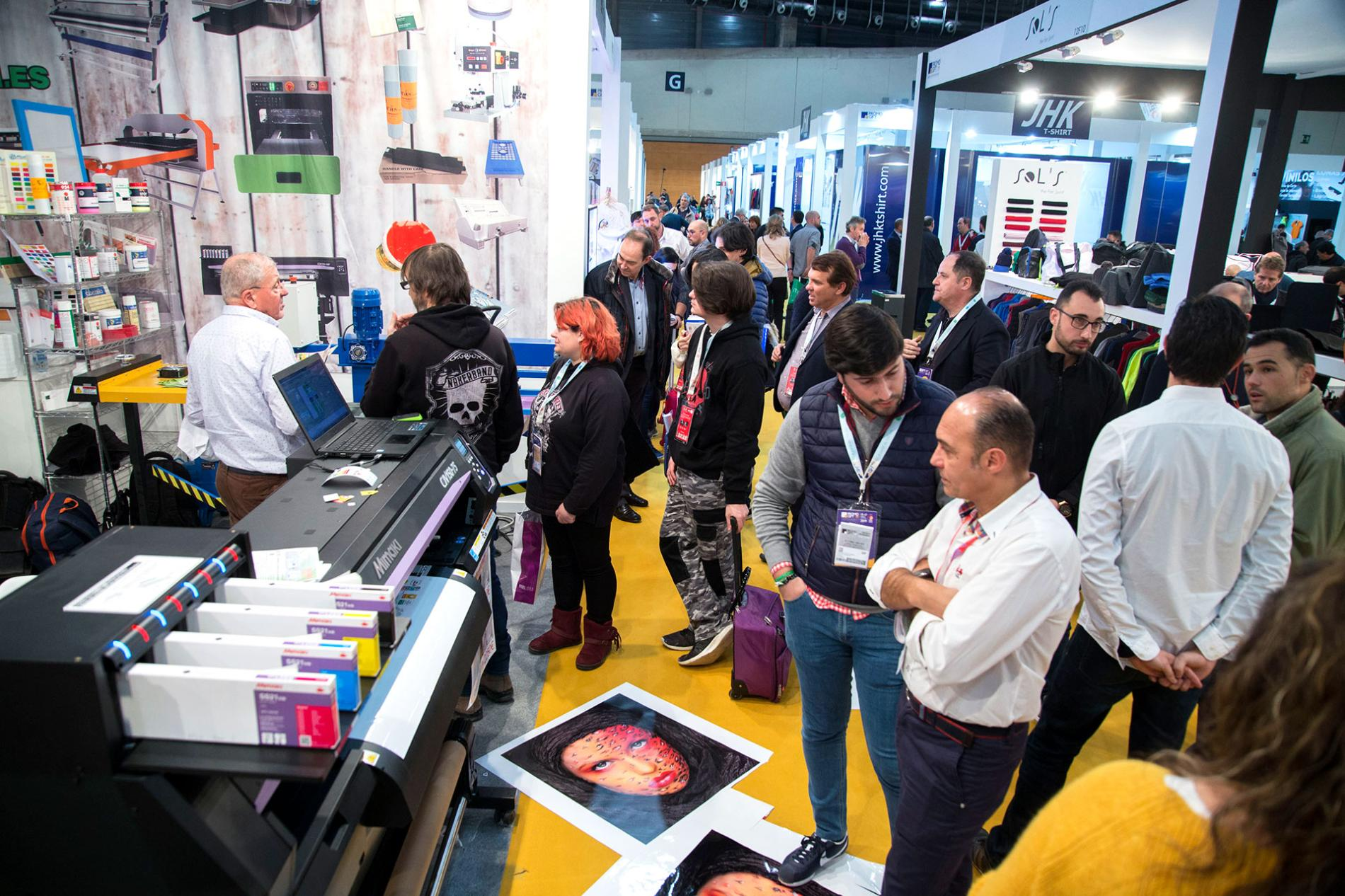 Visitantes frente a una maquina de impresión