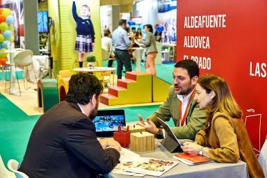 Dos expositores hablan con un visitante sentados a una mesa