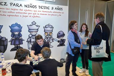 Niños jugando al ajedrez frente a un stand