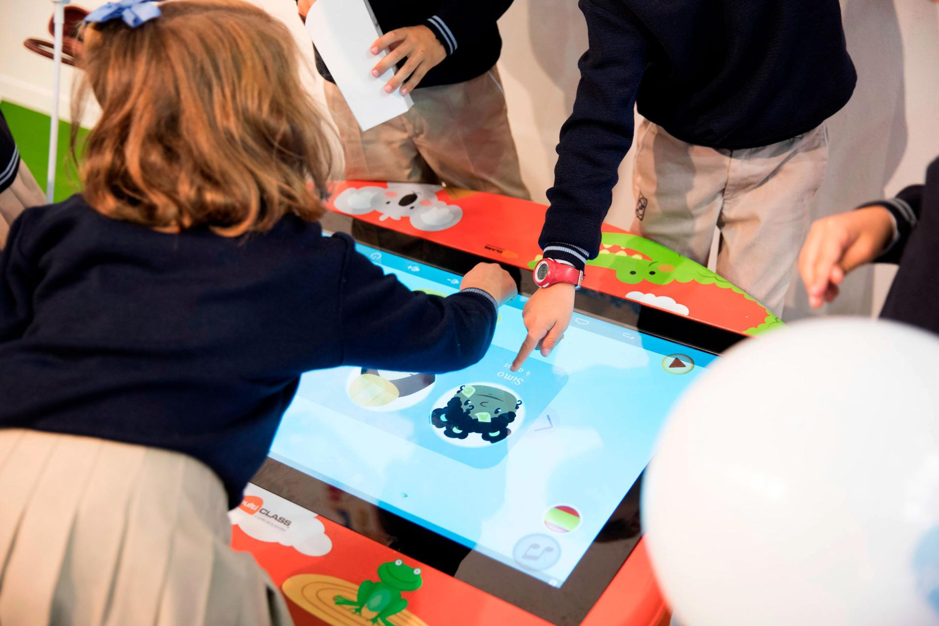 Children playing with interactive screen