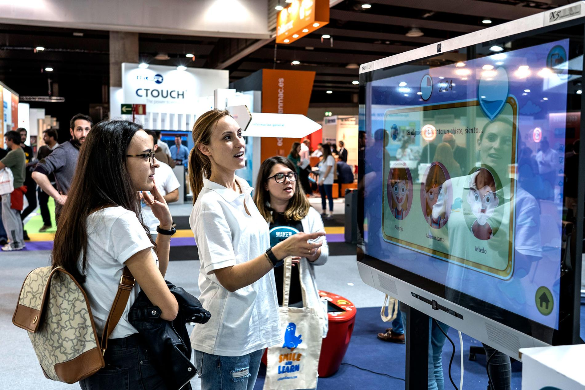 Visitantes mirando pantalla interactiva