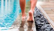 Pies descalzos caminando por el borde de una piscina