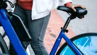 Una mujer sosteniendo una bici eléctrica
