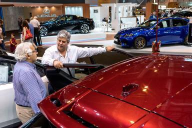 dos hombres apoyados sobre un coche rojo