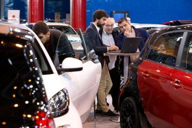 visitantes de la feria preguntando por las características de un coche